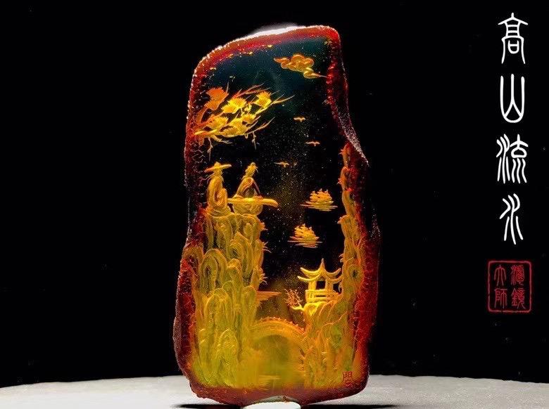 【高山流水】作品材质天然琥珀带原皮,刻画的是伯牙举目对望钟子期,只见海鸟翻飞,鸣声入耳;山林树木,郁