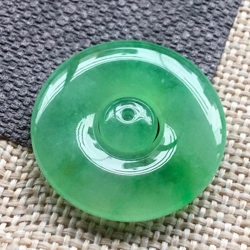 力荐款(室外自然光拍摄)老坑正冰种果阳绿色平安扣(搭配一颗同料顶珠),种水上乘,冰胶感十足,晶体结构致密,肉质水润细腻,莹润通透,起荧光、起强玻璃光泽。很清爽的绿色,相当漂亮,送人自留皆可。