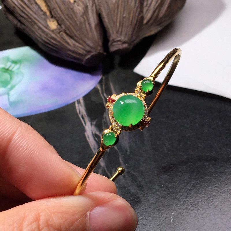 严选推荐老坑冰种翠绿色翡翠蛋面手镯,18k金钻镶嵌而成,种水上乘,冰胶感十足,晶体结构致密,起强玻璃光泽。颜色鲜亮,高性价比,值得入手品鉴。裸石尺寸约为:7.9-7.8-3.6毫米。备注:活口。