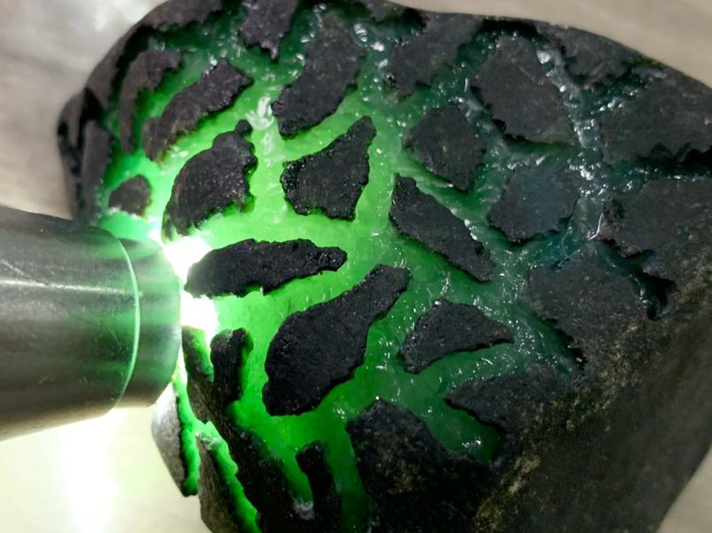342克莫湾基精品开窗料,皮壳黑亮有光泽局部带有腊皮,皮壳紧实,开窗处肉质细腻,起胶起荧,有糯化的感